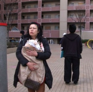 Млада майка с детето си напуска жилището, снимка на ЕРА/БГНЕС